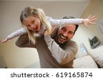 Small photo of Cute young daughter on a piggy back ride with her dad. Looking at camera.