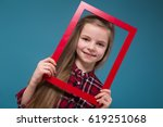 Small photo of Isolated on blue, attractive cute caucasian child in plaid shirt, and blue jeans with long bright hair show empty red frame, look throe the frame