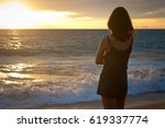young woman stands on the beach.... | Shutterstock . vector #619337774