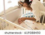 mother putting baby to sleep at ... | Shutterstock . vector #619388450