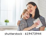 Small photo of Happy mother's day! Child daughter congratulates mom and gives her postcard. Mum and girl smiling and hugging. Family holiday and togetherness.