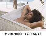 african man laying in hammock | Shutterstock . vector #619482764