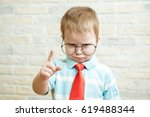 Small photo of Serious boy standing with a finger in big glasses. The concept of the evil boss.