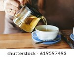 woman is pouring green tea from ... | Shutterstock . vector #619597493