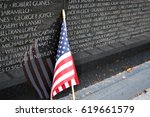 An American Flag leaned up against the Vietnam Memorial with the names of the solders who died in the war.