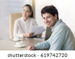 smiling guy sitting at office... | Shutterstock . vector #619742720