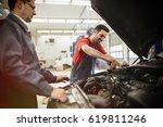 car mechanics working on car... | Shutterstock . vector #619811246
