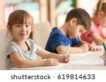 cute kids drawing in classroom | Shutterstock . vector #619814633