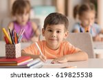 cute boy drawing in classroom | Shutterstock . vector #619825538