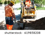 Small photo of men operating a mini digger in a street
