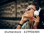 happy young woman listening to... | Shutterstock . vector #619906484