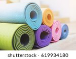 yoga mats on the wood table | Shutterstock . vector #619934180