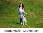 Stock photo teenage girl is walking with two husky dogs in a park 619980284