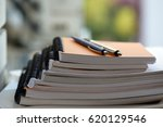 stack of notebooks with pens on ... | Shutterstock . vector #620129546