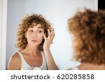 young curly woman using skin... | Shutterstock . vector #620285858