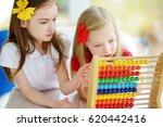 two cute little girls playing... | Shutterstock . vector #620442416
