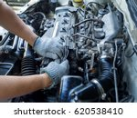 Small photo of Car mechanic working in auto repair service