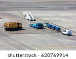 Small photo of Airfield universal cleaning machine, pushback tug, passenger boarding steps vehicle, tractor with baggage carts and minivan at the airport apron