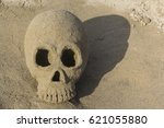 Small photo of Skull, built of sand, at a beach in Tuscany, Italy