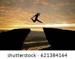 man jumping over precipice... | Shutterstock . vector #621384164