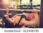 woman training on bench press | Shutterstock . vector #621448730