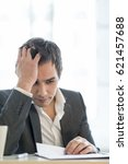 Small photo of Businessman working at office desk reading a report or document looking a bit stressed and agitated.