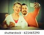Small photo of Smiling mother and adult son photographing together at home
