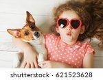 Stock photo little girl with her puppy jack russell terrier lying on a wooden floor toning instagram filter 621523628