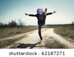 Crazy clown jumping and laughing on the road. Horizontal photo with cross-processing effect - stock photo