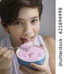 teenager boy eating pink yogurt ... | Shutterstock . vector #621894998