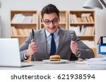 hungry funny businessman eating ... | Shutterstock . vector #621938594