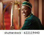 smiley young bellboy pushing... | Shutterstock . vector #622119440