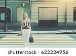 Stock photo smiling tall beautiful adult woman passing crosswalk on summer springtime cheerful blonde lady 622224956