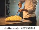 cook preparing pizza in kitchen | Shutterstock . vector #622254044