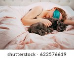 Stock photo tired woman with her cat in bed 622576619