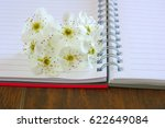 Small photo of Love lyrics diary. Open blank notebook with spring flower blossom. Romance message letter book. Copy space text place.