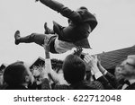 Small photo of men tossing up groom at stylish wedding reception. groomsmen having fun and throwing up in air. emotional funny moment, space for text. joyful friends. black white photo