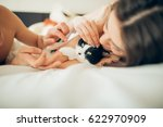 Stock photo family couple white lies on the bed caressing a cat in the middle looking at the camera close up 622970909