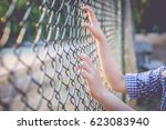 Hand Grasping A Wire Fence In...