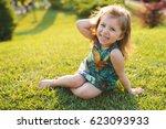 charming girl sitting on grass... | Shutterstock . vector #623093933
