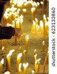 a woman hand lighting candles...   Shutterstock . vector #623133860