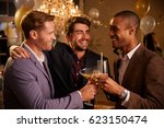 male friends make toast as they ... | Shutterstock . vector #623150474