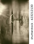 Small photo of Closeup of an old wooden door ajar with the key in the lock and with lens flare effect, textured in sepia tones for a vintage style with copy space.