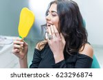 lady checking teeth in mirror.... | Shutterstock . vector #623296874