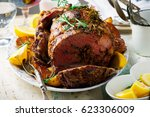 roast lamb leg with vegetables... | Shutterstock . vector #623306009