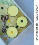 """Small photo of Yellow dessert """"Junket"""" from milk and rennet extract with turmeric in glasses on light background. Jelly-like pudding made from sweet cottage cheese. Healthy food. Space for text"""