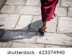 Small photo of Feet ot a buddhist monk wearing sandals and traditional red robe walking in the midday sun with a strongly defined shadow. Kopan monastery, Kathmandu, Nepal.