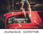 mechanic working on classic car ... | Shutterstock . vector #623507438