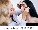 make up artist does makeup to a ... | Shutterstock . vector #623529158