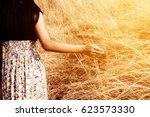girl walking in grass field | Shutterstock . vector #623573330